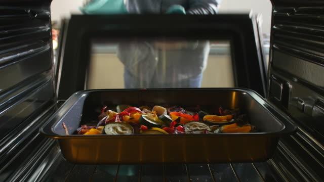 vídeos de stock e filmes b-roll de homem tomando tabuleiro de assado produtos hortícolas fora da fornalha - cooker happy