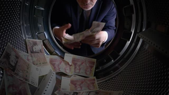 POV Man taking UK pounds out of a washing machine video