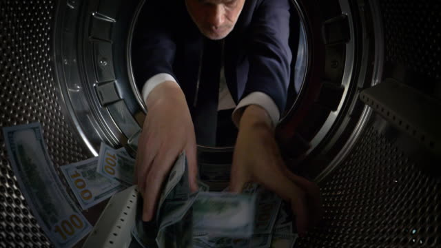 POV Man taking US dollars out of a washing machine video