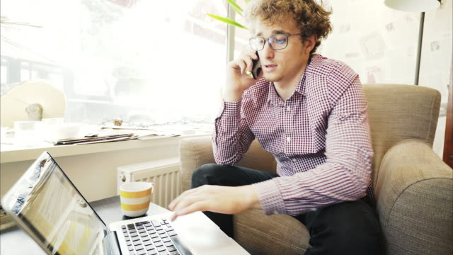 man talking at phone while using a laptop. - owner laptop smartphone video stock e b–roll