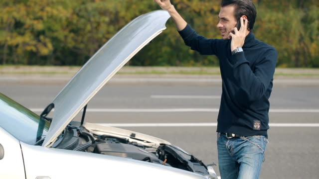 Man talking on a cell phone by a broken car Road trip car trouble. A young man with a silver car that broke down on the road. towing stock videos & royalty-free footage