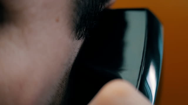 A man talking on a telephone A man talking on a telephone. Closeup landline phone stock videos & royalty-free footage
