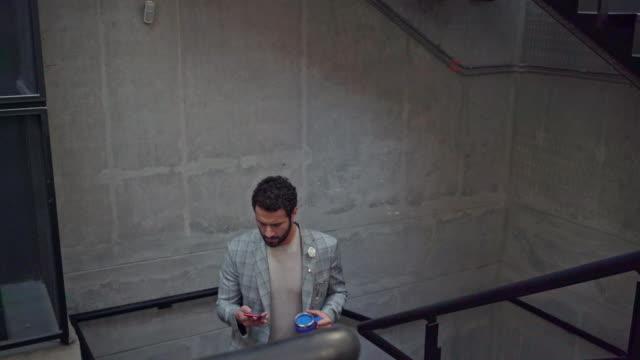 mann spricht auf seinem handy im büro - lateinische schrift stock-videos und b-roll-filmmaterial