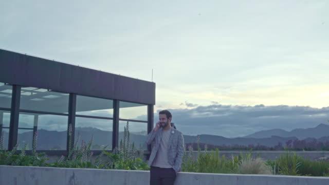 mann spricht auf seinem handy auf dem dach im büro - lateinische schrift stock-videos und b-roll-filmmaterial