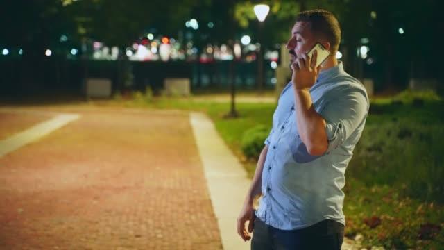 mann auf seinem smartphone im freien in der nacht im öffentlichen park - online dating stock-videos und b-roll-filmmaterial