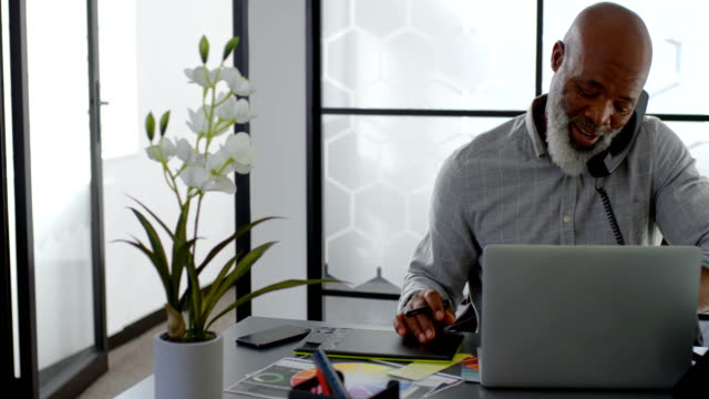 Man talking on landline while using laptop on desk 4k Man talking on landline while using laptop on desk at office 4k landline phone stock videos & royalty-free footage