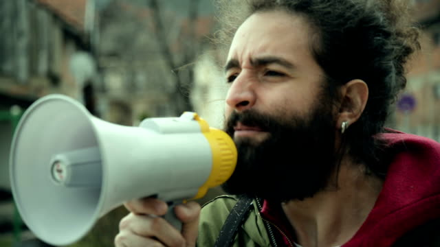 Man talking on megaphone Young, bearded man talking and yelling on megaphone. megaphone stock videos & royalty-free footage