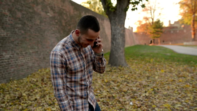 Man talking on mobile phone in autumn video