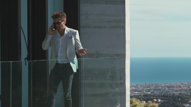 vídeos de stock e filmes b-roll de man talking on mobile phone - mansão imponente
