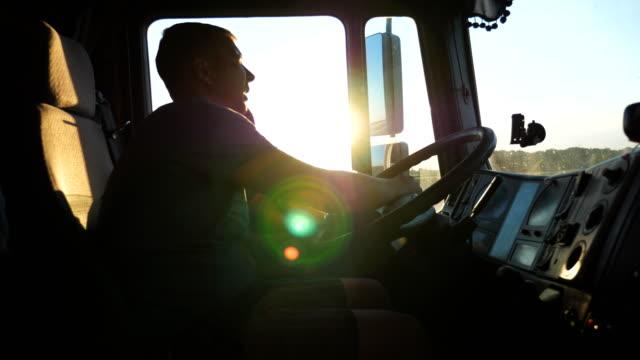 vídeos y material grabado en eventos de stock de hombre hablando por teléfono móvil mientras se conduce un camión. chico caucásico es montar a caballo por el campo sobre fondo puesta de sol. perfil de conductor de camión. lado más lenta cerca - conductor de autobús
