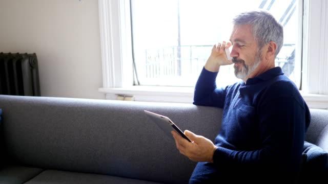 Man talking on mobile phone while using digital tablet in living room 4k