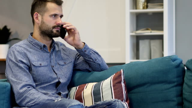 man talking on phone, sitting on couch in bedroom - rispondere video stock e b–roll