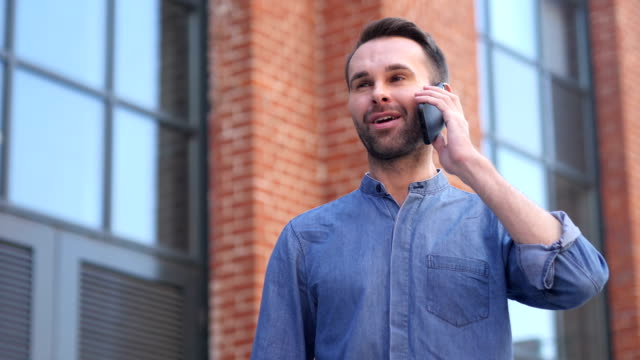 Man Talking on Phone while Standing Outside Office Building, Discussing video