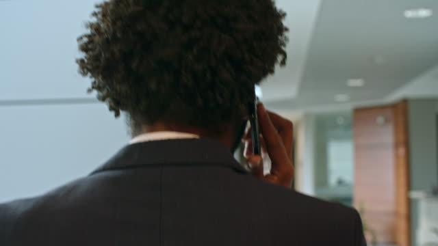 man talking on phone while walking through office center - call center стоковые видео и кадры b-roll