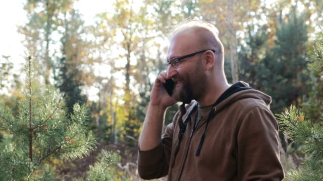 Man talking on the phone in the Park, against the trees Bearded man with glasses talking on the phone fun in the Park, against the autumn landscape pigtails stock videos & royalty-free footage