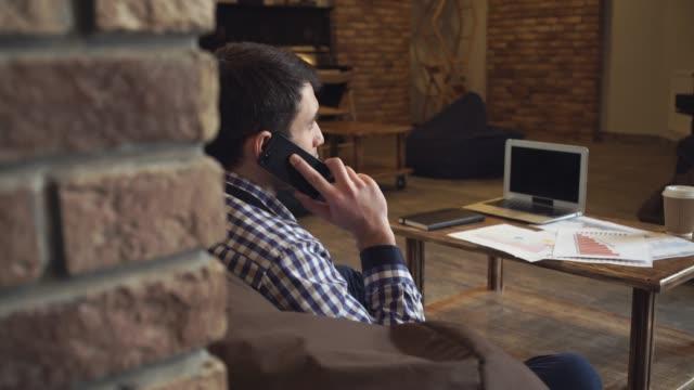 vídeos de stock e filmes b-roll de homem um falar ao telefone sentado na mesa é um computador portátil - coffee table