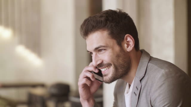 Man talking on the phone A businessman is talking on the phone while sitting down. handsome people stock videos & royalty-free footage