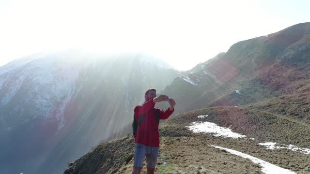 Man talking selfies form mountain top video
