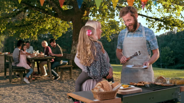 slo mo man talking to his wife and his daughter while barbecuing - alla griglia video stock e b–roll