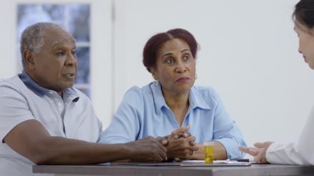mężczyzna rozmawia z kobietą lekarza - mąż filmów i materiałów b-roll