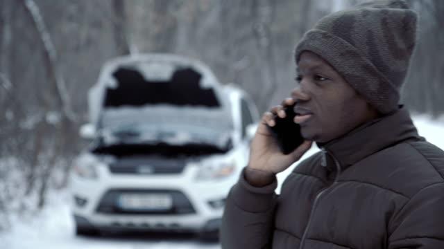 vídeos de stock e filmes b-roll de man talking with helpline having broken car - berma da estrada