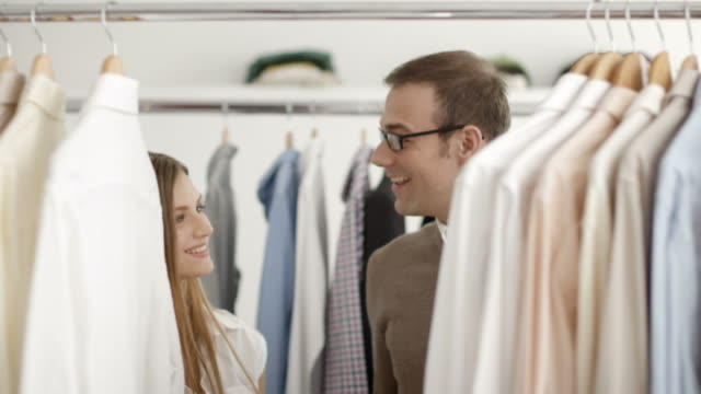 Man talking with sales assistant in clothes shop Customer speaking to sales manager in fashion store while shopping for clothes. button down shirt stock videos & royalty-free footage