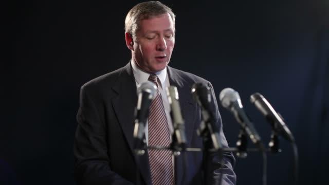 vídeos y material grabado en eventos de stock de hombre habla en micrófonos en la conferencia de prensa - político