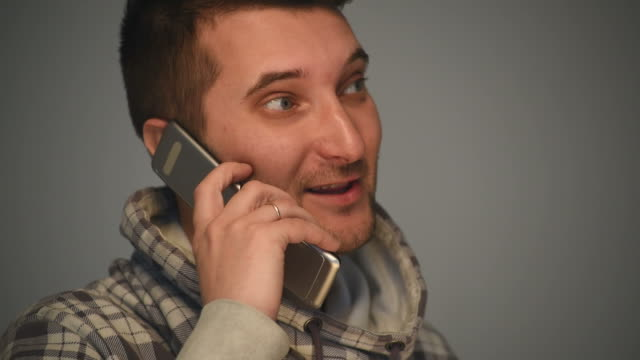 Man talks on mobile phone Young man talks on mobile phone on grey background young singles stock videos & royalty-free footage