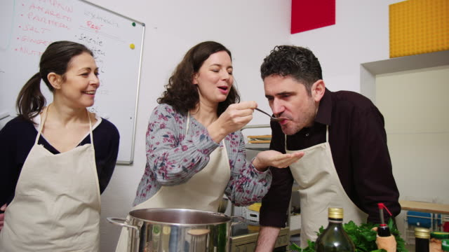 Man tasting the recipe made by woman at cooking class
