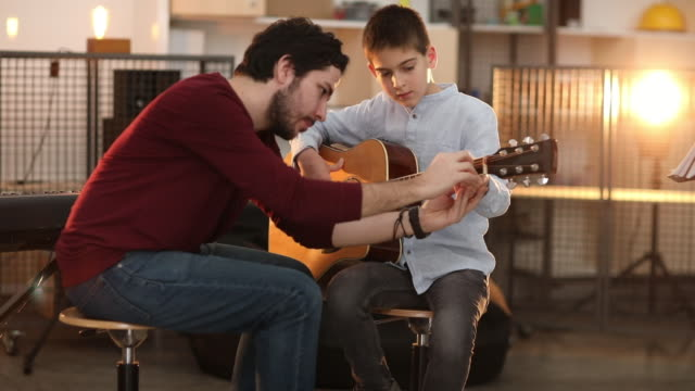 Man teaching a little boy how to play guitar