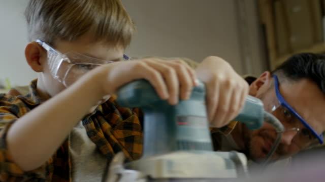 stockvideo's en b-roll-footage met man onderwijs jongen te gebruiken van de gordel sander - elektrisch gereedschap