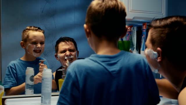 vídeos de stock e filmes b-roll de man teaching son shaving face - crianças todas diferentes