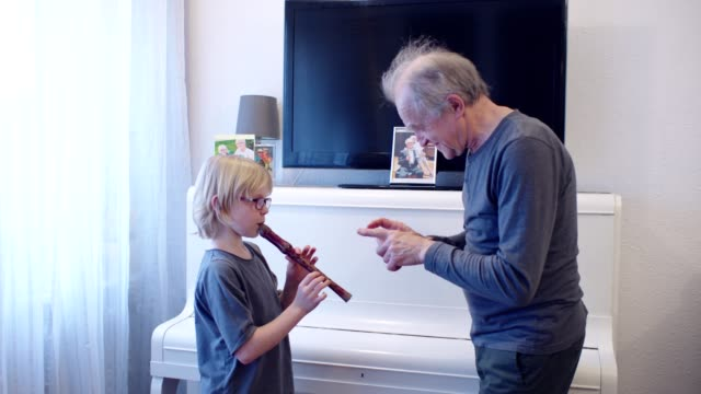 Man (grandfather) teaching young boy how to play flute.