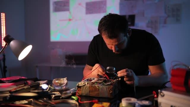 Man terrorist constructing a bomb in workshop