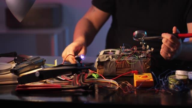 Man terrorist making a bomb in workshop