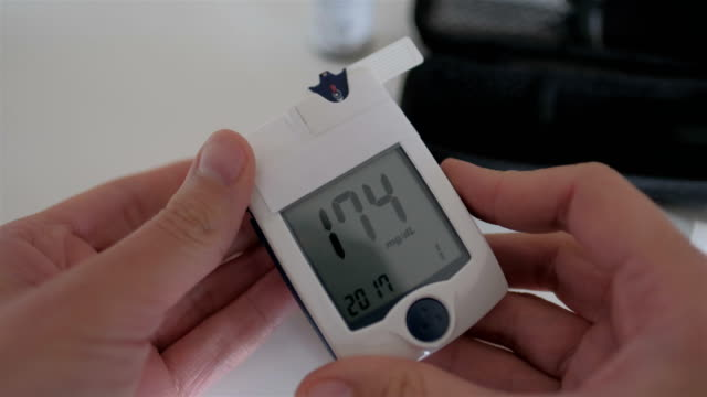 man testing his blood sugar - diabetes стоковые видео и кадры b-roll