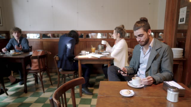 Man text messaging on mobile phone while drinking coffee at cafe Man text messaging on mobile phone while drinking coffee at cafe suit videos stock videos & royalty-free footage