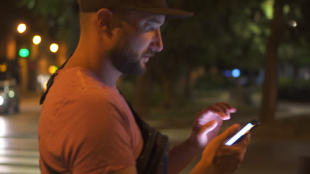 Man texting using app on smartphone at night in city