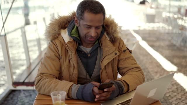 vídeos de stock e filmes b-roll de man texting via smartphone in outdoor cafe - esplanada portugal