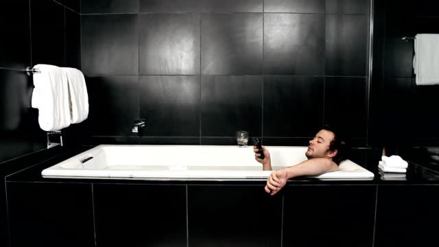 stockvideo's en b-roll-footage met man texts in bathtub - hd - cell phone toilet