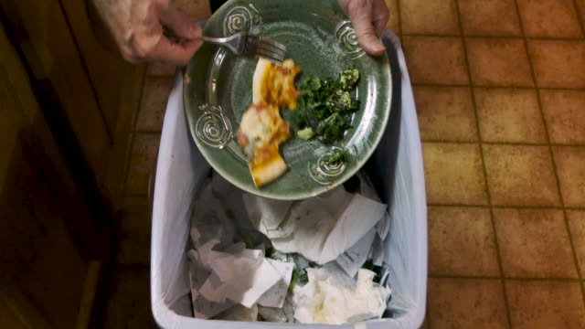 Man throwing away uneaten leftover food into a trash can