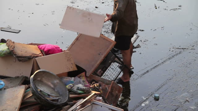 Man throwing household waste from flood situation. video