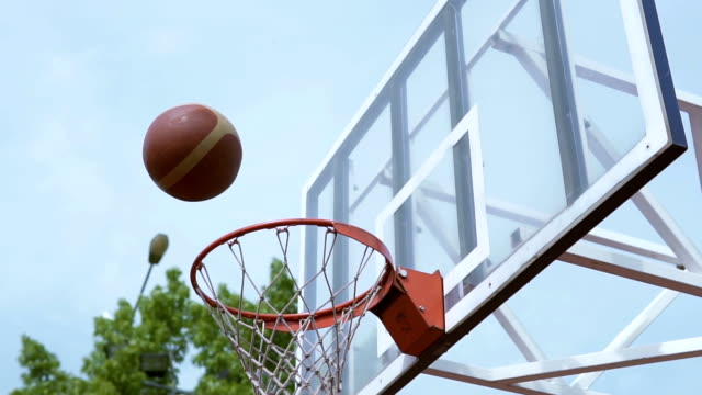 Man throws ball in the basketball basket - vídeo