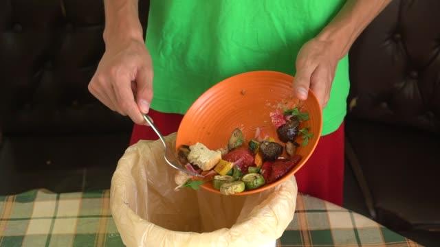 en man kastar rester av en grönsak vegetarisk måltid från en tallrik till en kompost hink - food waste bildbanksvideor och videomaterial från bakom kulisserna