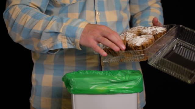 男はゴミ箱にカップケーキやマフィンを投げ捨てます。 ビデオ