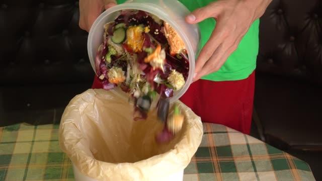 mann wirft gemüsepeeling, fetzen und fruchtschalen in einen komposteimer - food stock-videos und b-roll-filmmaterial