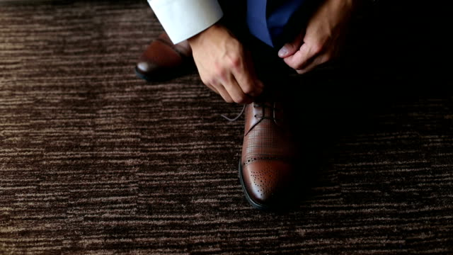 Man ties up shoelaces on brown leather shoes. video