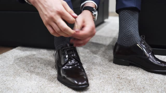 Man ties up shoelaces on brown leather shoes video