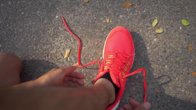 結び目のレースのスポーツシューズを締める男、ワークアウトのためのradyと午前中に実行 - 結ぶ点の映像素材/bロール