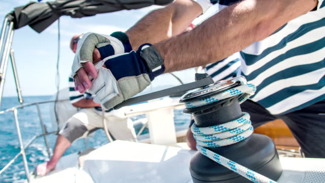 MS TU Man Tightening The Sail HD1080p: MEDIUM TILT UP shot of a man tights a rope around a winch while some other passengers sitting behind him on a deck of a sailboat. Also available in 4K resolution. regatta stock videos & royalty-free footage